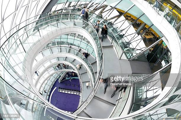 A winding stairwell and people in motion at London City Hall