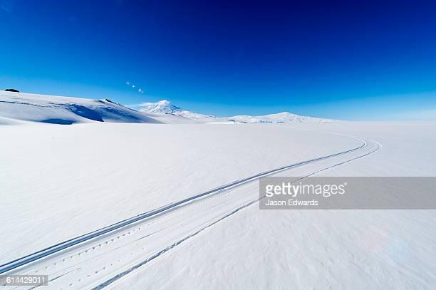 Skiddoo tracks cross the snow on the vast barren Ross Ice Shelf.