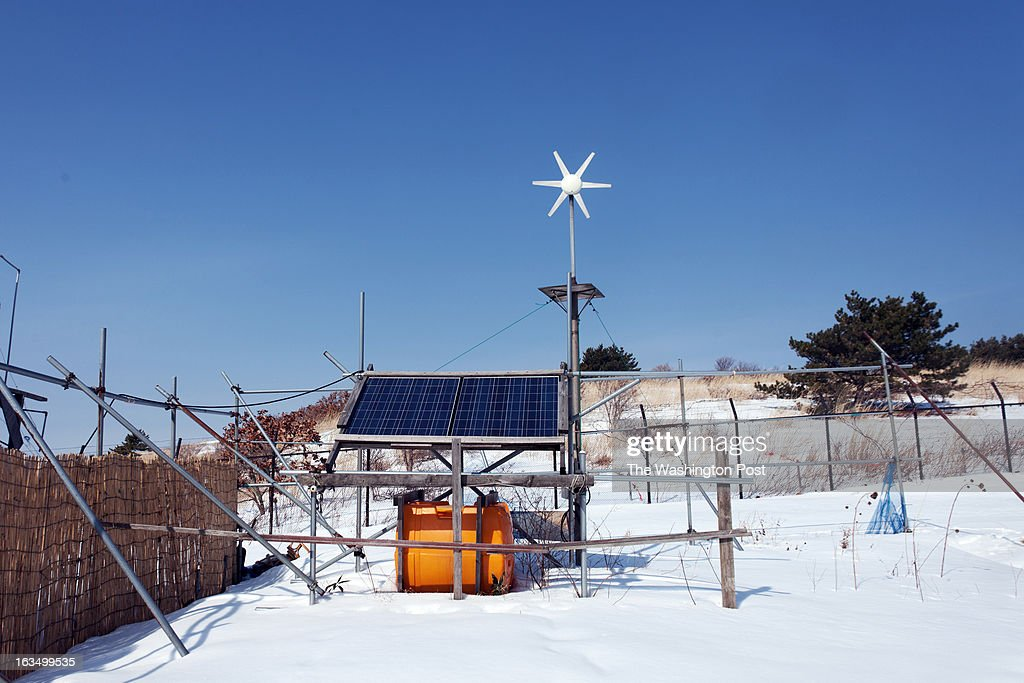 A windmill and a solar panel to generate power at the Asako House, a log house built in a piece of property owned by Atsuko Ogasawara. The house is surrounded by the land owned by Oma Nuclear Power Plant builder, J-Power.