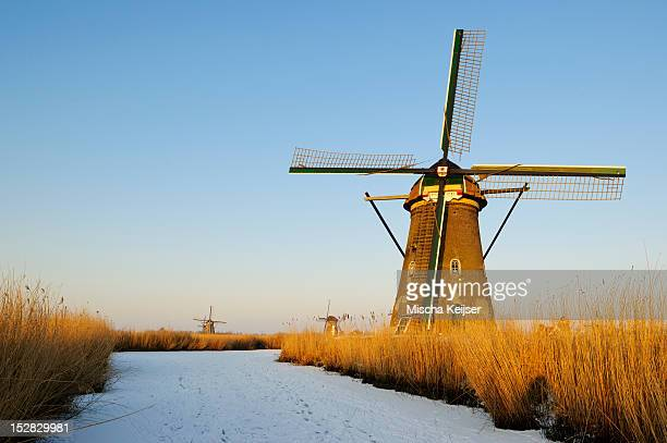 Windmill by river in rural landscape