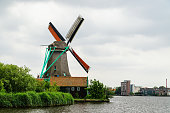 Windmill in Zaanse Schans near Amsterdam with dramatic storm clouds, Netherlands. Travel theme.