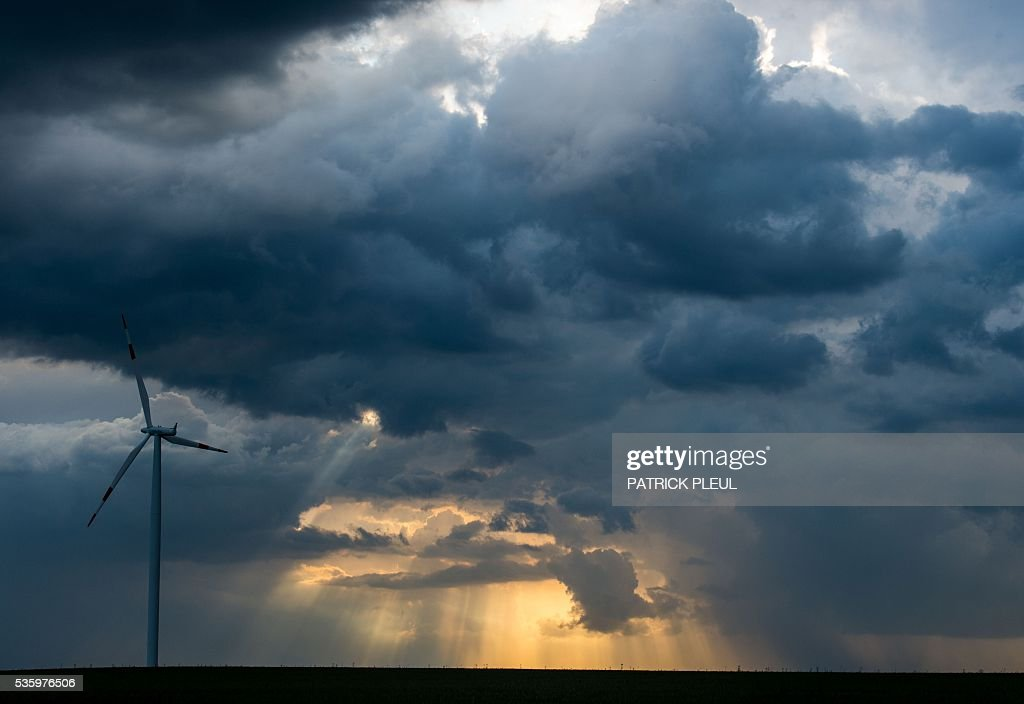 A windmill is seen on a meadow as sun shines through dark clouds of a thunder cell near Sieversdorf, northeastern Germany, on May 30, 2016. / AFP / dpa / Patrick Pleul / Germany OUT