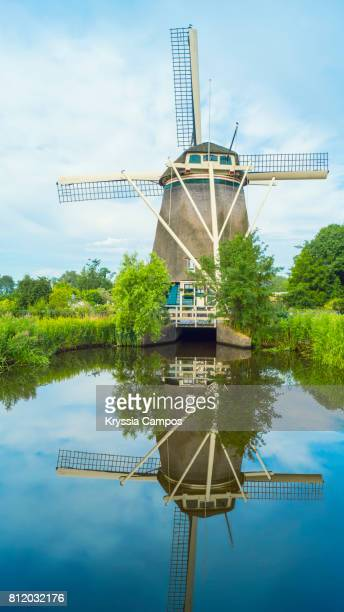 Windmill reflecting in still canal, Netherlands