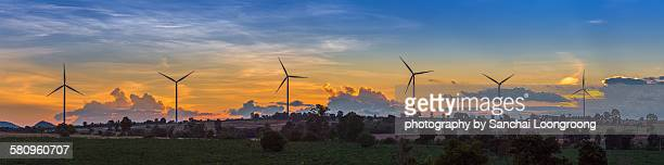 Windmill turbines in a hilly landscape at sunset