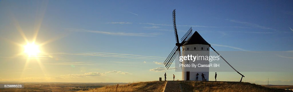 Windmills in the sunset, people play with the Sun