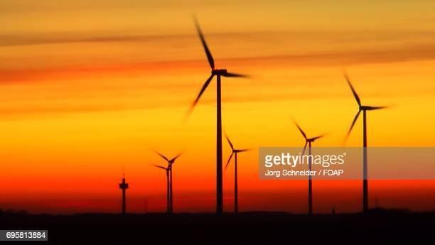 Windmills on landscape during sunset