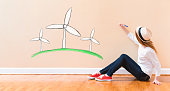 Windmills with young woman holding a pen on floor