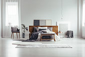 Wooden bench and grey chair near king size bed against white wall with copy space in bedroom with window and paintings