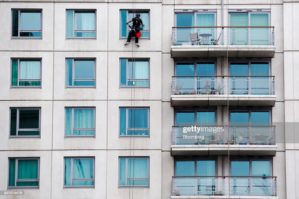 A window cleaner abseils down the face of a building whilst cleaning the windows of an aprtment block in the Nine Elms district in London, U.K., on Tuesday, Aug. 22, 2017. Billionaire Wang Jianlins Dalian Wanda Group Co. scrapped plans to buy a land plot in London for 470 million pounds ($606 million) amid the Chinese governments intensifying scrutiny of overseas investments. Photographer: Luke MacGregor/Bloomberg via Getty Images