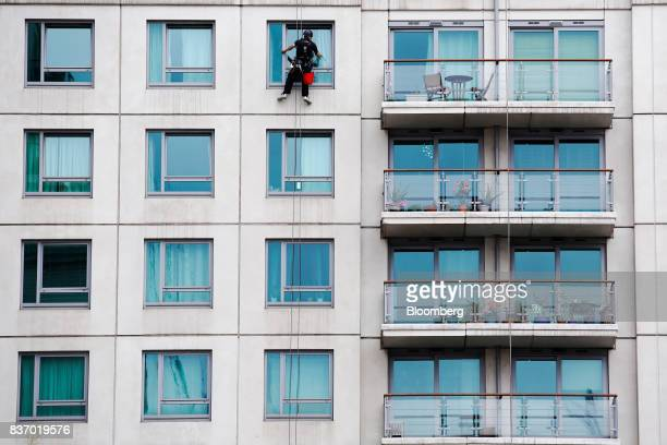 A window cleaner abseils down the face of a building whilst cleaning the windows of an aprtment block in the Nine Elms district in London UK on...
