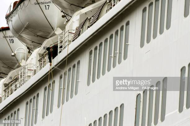 A window cleaner has the daunting task of cleaning windows on the QE2 after it arrived at the Ocean Terminal in Greenock