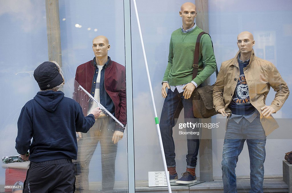 A window cleaner washes a glass window displaying men's mannequins at a fashion clothes store in Croydon, south London, U.K., on Monday, Feb. 10, 2014. Westfield Group, Australia's biggest mall operator, and Hammerson Plc won preliminary approval to rebuild the Whitgift Centre mall in south London as part of a project valued at about 1 billion pounds ($1.6 billion). Photographer: Jason Alden/Bloomberg via Getty Images