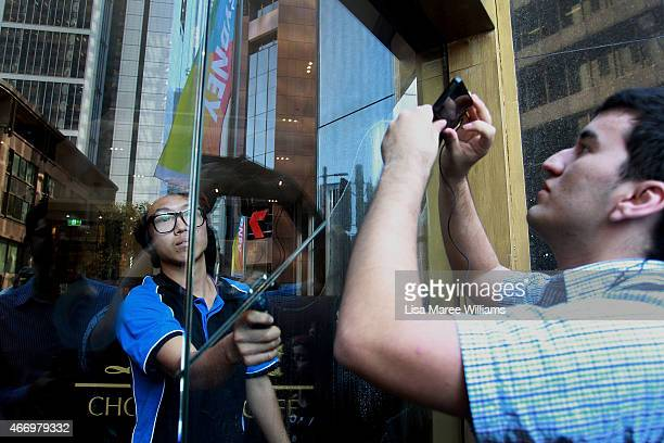 A window cleaner wipes the entrance doors of the Lindt Cafe in Martin Place on March 20 2015 in Sydney Australia The cafe reopened to the public...