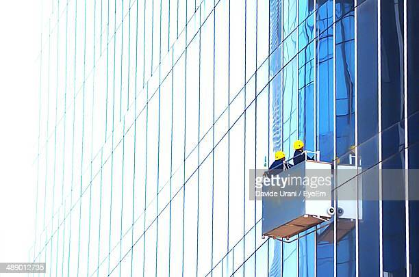 Window cleaners cleaning office building