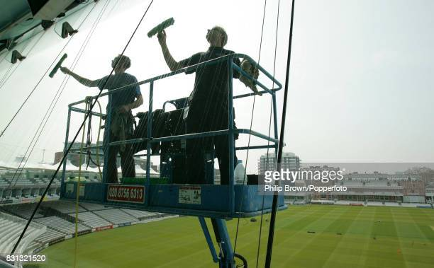 Window cleaners cleaning the windows of the Media Centre at Lord's in preparation for the first match of the season between MCC and the County...