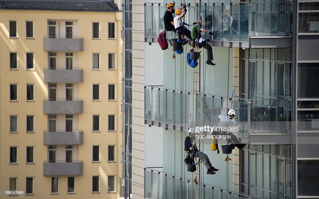 Window cleaners on zip lines are seen as they clean the glass railings on the balconies of the 'Platinum Towers' in Warsaw on May 6, 2013. The twin tower apartment complex is situated adjacent to the city centre in with many similar buildings for both business and residential luxury apartments are springing up in the Polish capital.