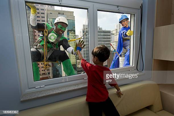 Window cleaners wearing superhero costumes greet a patient at a Children's Hospital as part of the celebration of Children's Day in Sao Paulo Brazil...