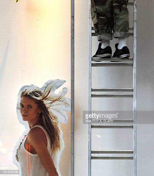A window dresser stands on a ladder as he hangs some of the summer clothes at HM on 5th Avenue in New York May 18 2010 AFP PHOTO /TIMOTHY A CLARY