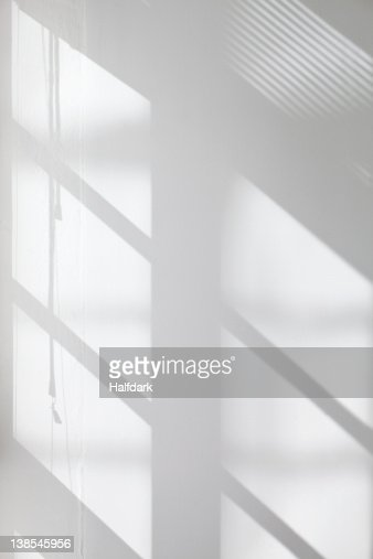 Window glass, blinds and pulley shadows on wall