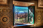 An ornate window in the Kasbah Telouet in Morocco overlooks the fields and Atlas Mountains