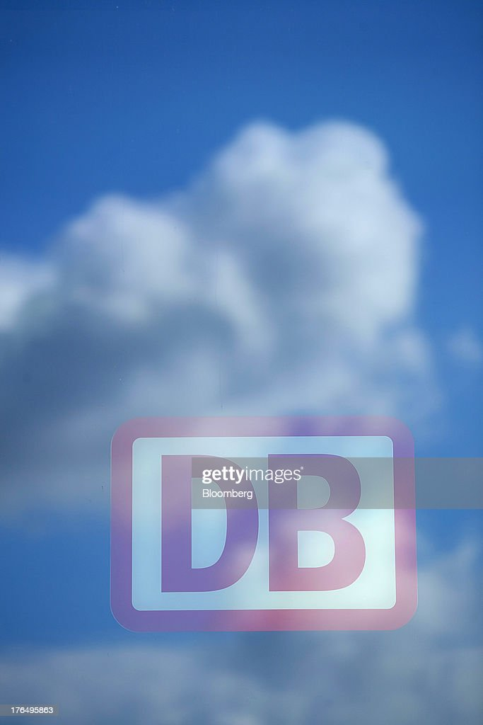 A window reflects clouds as the logo of Deutsche Bahn AG is displayed outside Berlin Central Station, also known as Hauptbahnhof, in Berlin, Germany, on Tuesday, Aug. 13, 2013. German gross domestic product rose 0.7 percent from the first quarter and the French economy expanded 0.5 percent, the countries' national statistics offices said today. Photographer: Krisztian Bocsi/Bloomberg via Getty Images