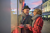 Mature couple are window shopping in the festive city centre at christmas time.