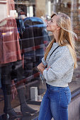 Window shopping babe in grey sweater and jeans