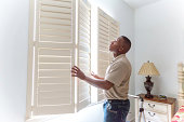 A window treatment installer installs wooden shutters in a residential home.  RM