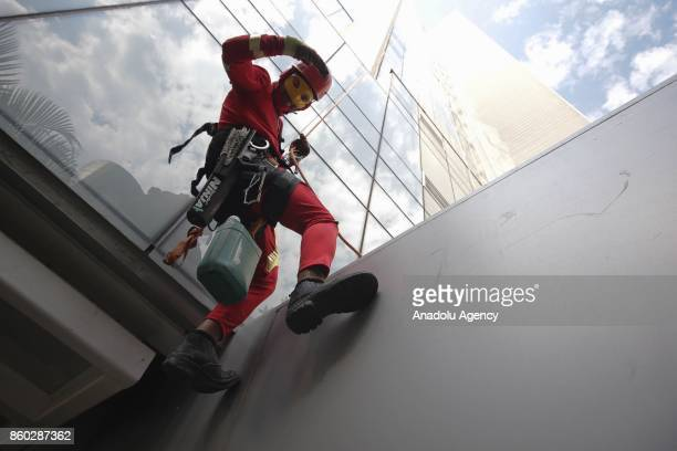 A window washer dressed as Iron Man prepares to abseil the windows of a hospital specializing in cancer treatment at Angelica Avenue in Sao Paulo...