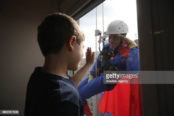 A window washer dressed as Superman abseils the windows of a hospital specializing in cancer treatment as he greets a child patient at Angelica...