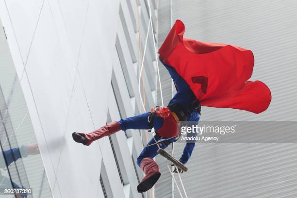 A window washer dressed as Superman prepares to abseil the windows of a hospital specializing in cancer treatment at Angelica Avenue in Sao Paulo...