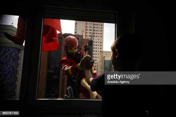 A window washers dressed as Iron Man abseils the windows of a hospital specializing in cancer treatment as he greets a child patient at Angelica...