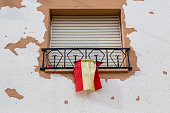 Window with closed blinds and Spanish flag, Humanes, Province of Guadalajara, Spain