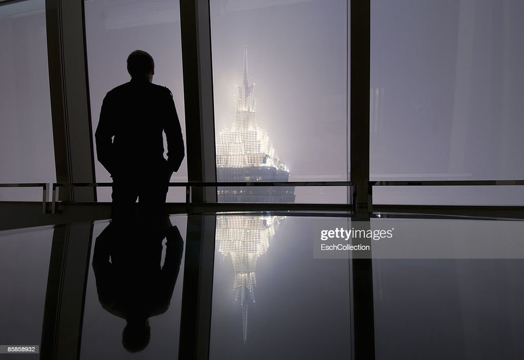 Window with man looking at the skyline of Shanghai : Stock Photo