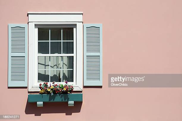 Window with pink background and windowbox.