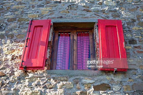 Window with red wooden shutters, Tuscany, Italy