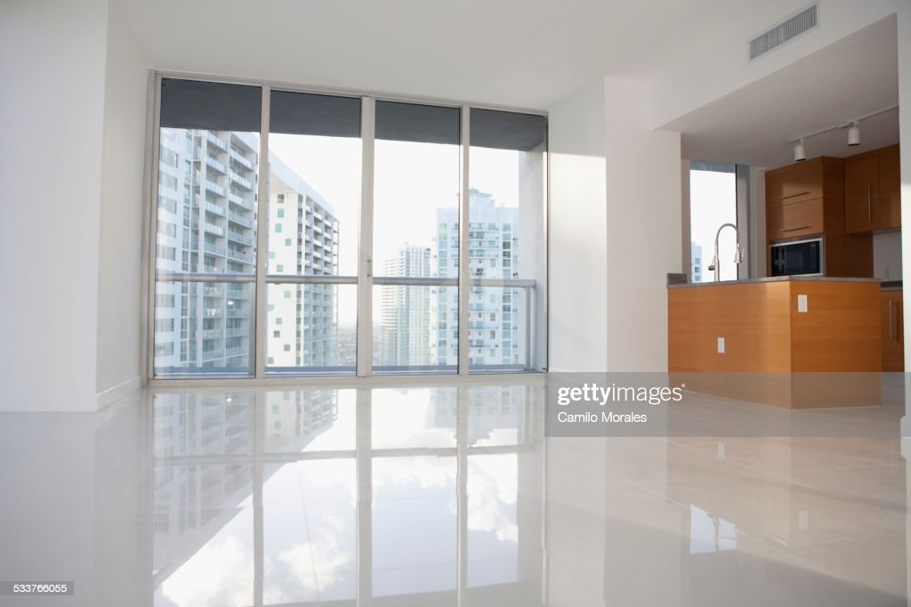 Windows and reflective floor in empty modern apartment