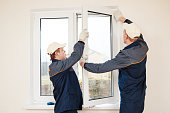 construction workers glaziers installing glass window indoor