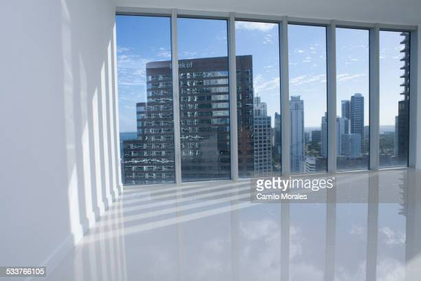 Windows overlooking cityscape in empty modern apartment