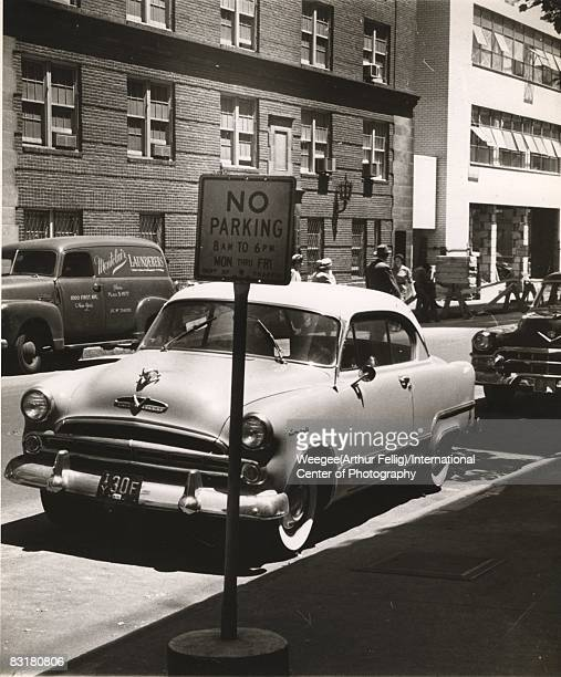 Windshield wipers hold two green $1500 parking tickets onto a car parked in the west 50th street area near a 'No Parking' street sign New York ca1951...