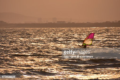 A windsurfer on the sunset beach : ストックフォト