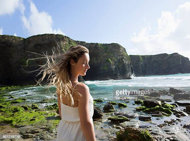 Windswept woman at beach with eyes closed