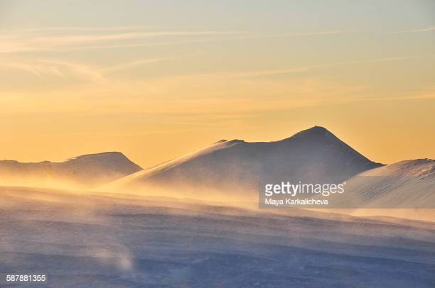 Windy sunset in a snowy mountain