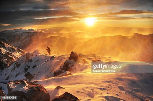 Windy winter sunrise at mountain summit