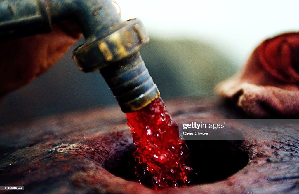 Wine being pumped into oak barrel. : Stock Photo