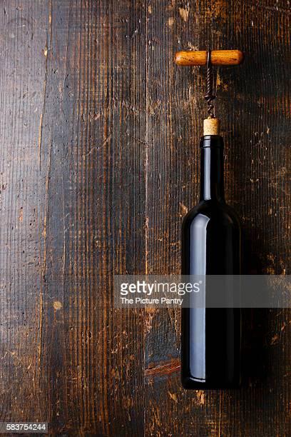 Wine bottle and corkscrew on dark wooden background