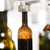 Wine bottle filling along a conveyor belt in a wine bottling factory