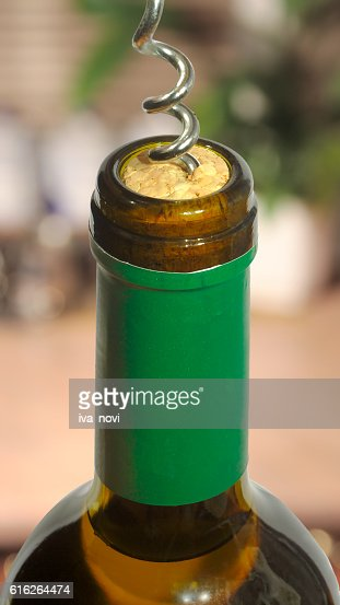 wine bottle with a cork and a corkscrew uncover : Stock Photo