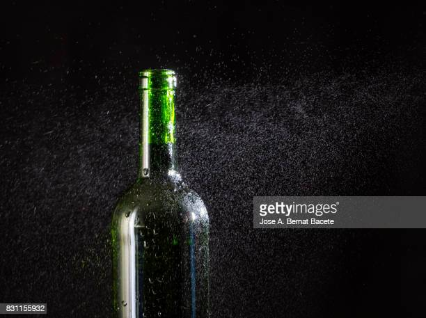 Wine bottle  with the frosted glass with drops of water and a steam cloud frozen on a black background
