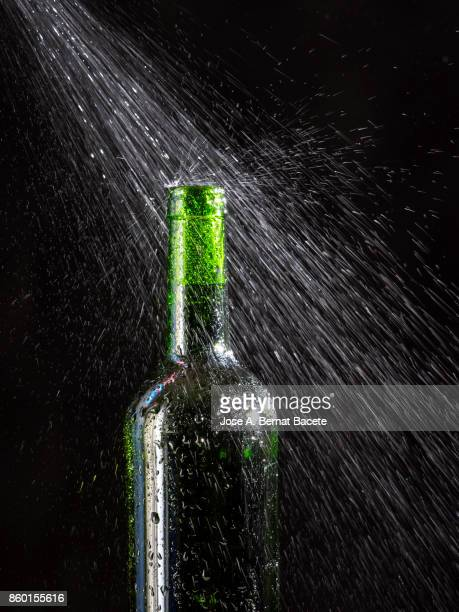 Wine bottle  with the frosted glass with drops of water and a steam cloud frozen on a black bottom